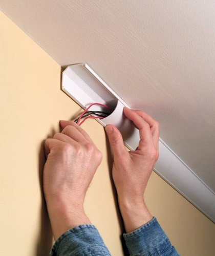 man installing a ceiling corner duct